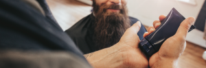 man smiling at barber pouring a product into his hand